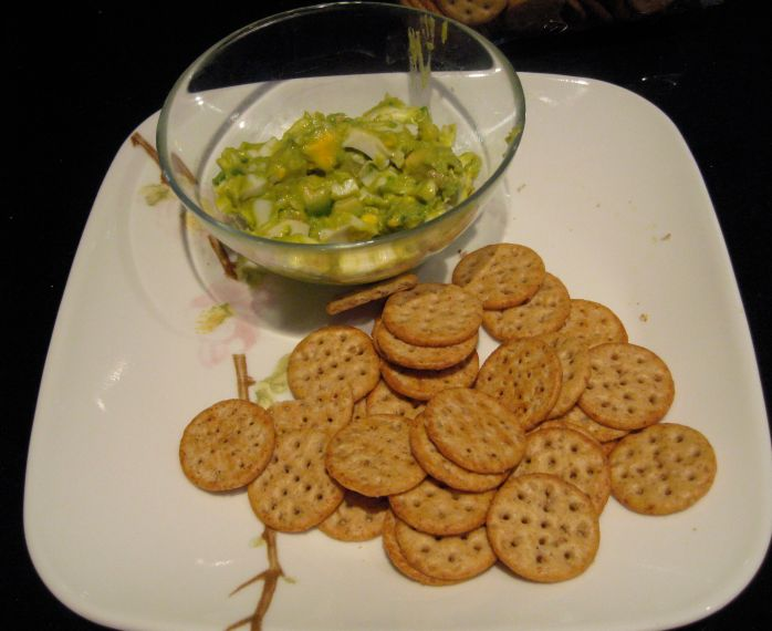 Egg salad with avocado and crackers